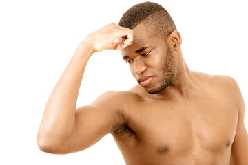 Man checking arm muscles, unhappy expression