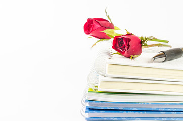 notebook stack with pen on white background