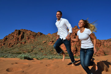 Couple Holding Hands and Running Through Sand