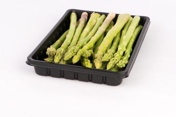 Fresh asparagus in black tray