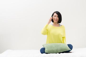 ベッドで電話する女性