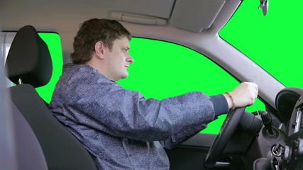 Man drives a car against a green background