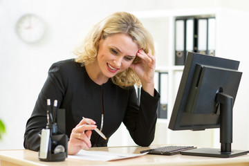 smiling business woman looks at document sitting at table in