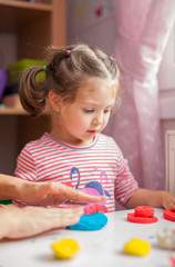 little cute girl playing with modeling clay in her playroom