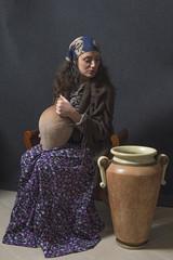 donna con scialle seduta vicino ad un' anfora