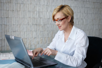 Blonde businesswoman in glasses typing