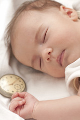 Sweet baby sleeps with  clock