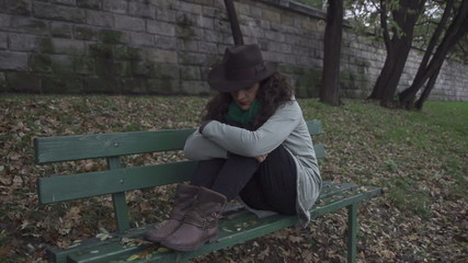 Lonely woman sitting on the bench, steadycam shot, slow motion