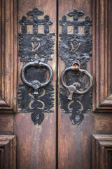handles of an ancient brown wooden door