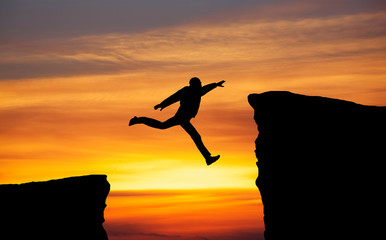 Man jumping across the gap from one rock to cling to the other.