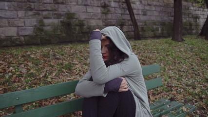 Sad woman in hoodie on boulevard, steadycam shot, slow motion