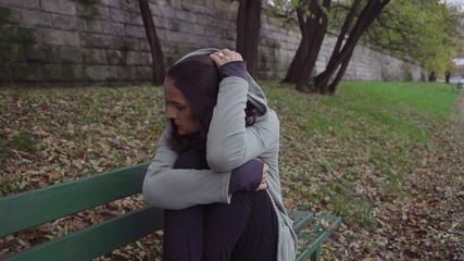 Sad woman in hoodie on boulevard, steadycam, slow motion shot