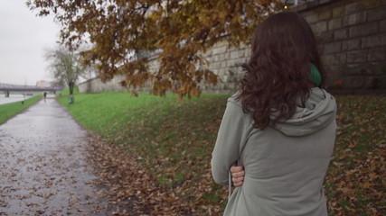 Woman walking on boulevard on gloomy day, steadycam, slow motion