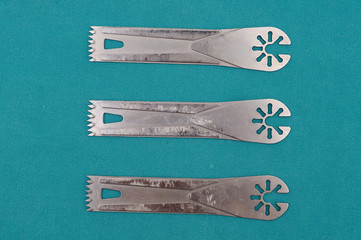 Surgery oscillating saw blades on green cloth.
