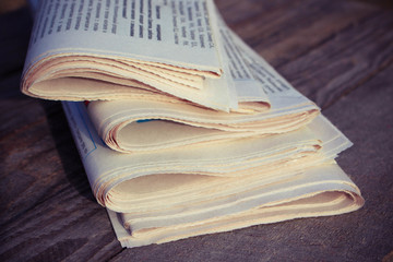 Newspapers on old wood background. Toned image.
