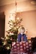 Kleiner Junge freut sich vor dem Christbaum über sein Geschenk