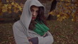 Sad woman hiding face in hood, steadycam shot, slow motion shot