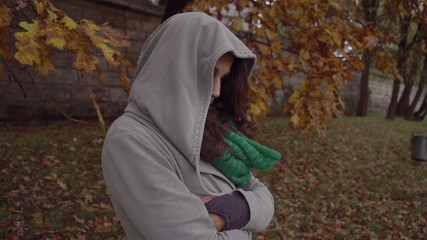 Sad woman hiding face in hood, steadycam shot, slow motion shot