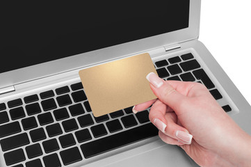 Woman holding gold credit card in hand. On-line shopping on the