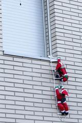 Santa climbing into a house