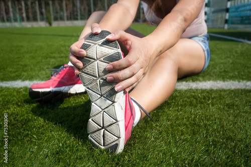 Foto op Plexiglas Luchtsport young woman warming up on grass before running