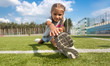 young girl stretching legs on soccer field at sunny day - 75303227