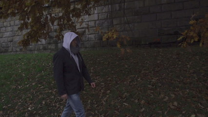 Man wearing hoodie on wintry day, steadycam shot, slow motion
