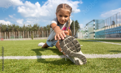 Foto op Plexiglas Luchtsport young girl stretching legs on soccer field at sunny day