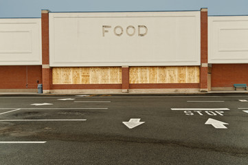 Boarded Up Out of Business Grocery Store At Dusk