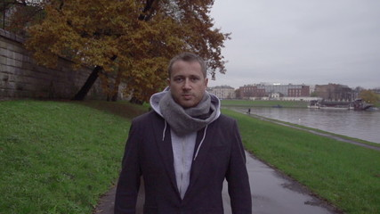 Man walking on boulevard next to  river, steadycam, slow motion