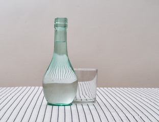 Rustic green glass carafe of water with drinking glass