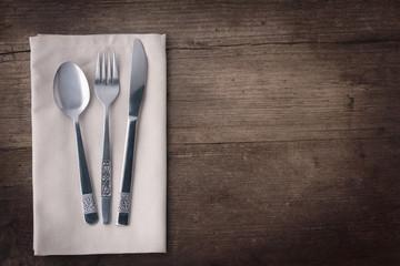 Besteck und Serviette auf Holztisch