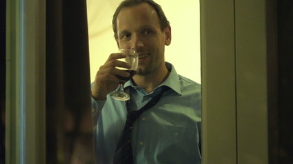 Happy, handsome man drinking red wine by window at home at night