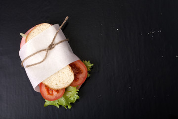 sandwich with sausage bandaged twine on a black background. With