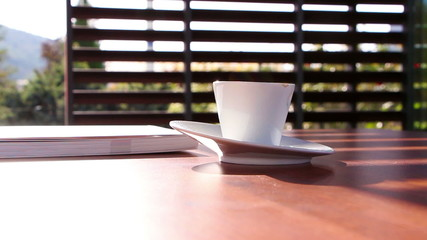 Book and a cup of coffee on a table in a pavilion with blinds
