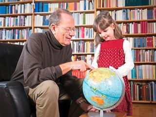 Großvater und Enkeltochter betrachten einen Globus