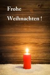 Frohe Weihnachten, rote Kerze brennt im Schnee vor Holzwand