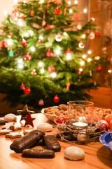 Tisch mit Weihnachtsgebäck vor Weihnachtsbaum