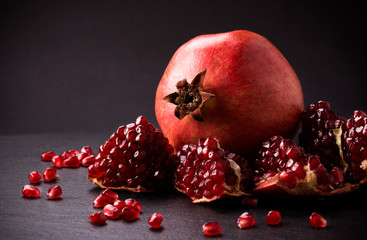 Some red pomegranates on black slate plate