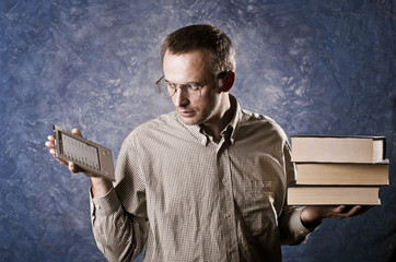 Man is comparing stack of books to e-book reader.