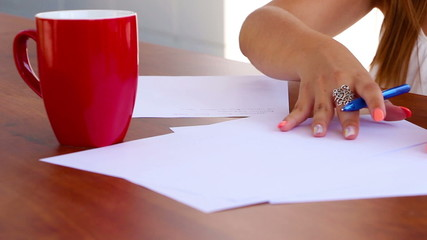Wind blows sheets of paper while woman is writing