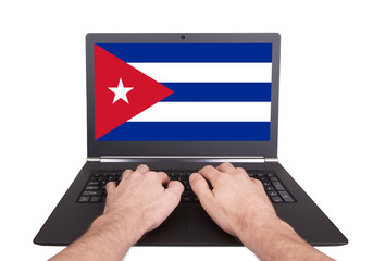 Hands working on laptop, Cuba