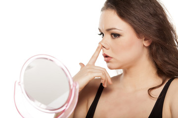 worried young woman in front of the mirror raises her nose