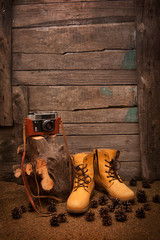 still life with boots and retro camera on wooden background