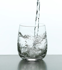Pouring water from bottle on  glass isolated on white