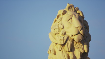 London Southbank lion as birds fly by during sunset