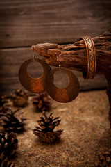 Beautiful gold bracelets and earrings on wooden background