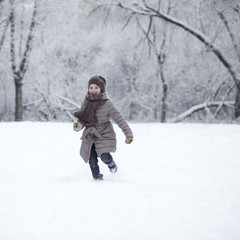 Happy little girl running on the background of snow covered wint