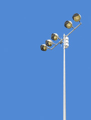 Outdoor stadium lights against daytime blue sky, vertical view