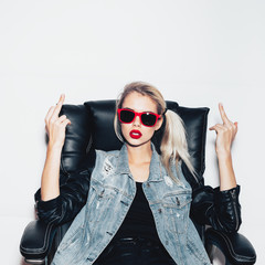 Young  woman in sunglasses showing middle finger